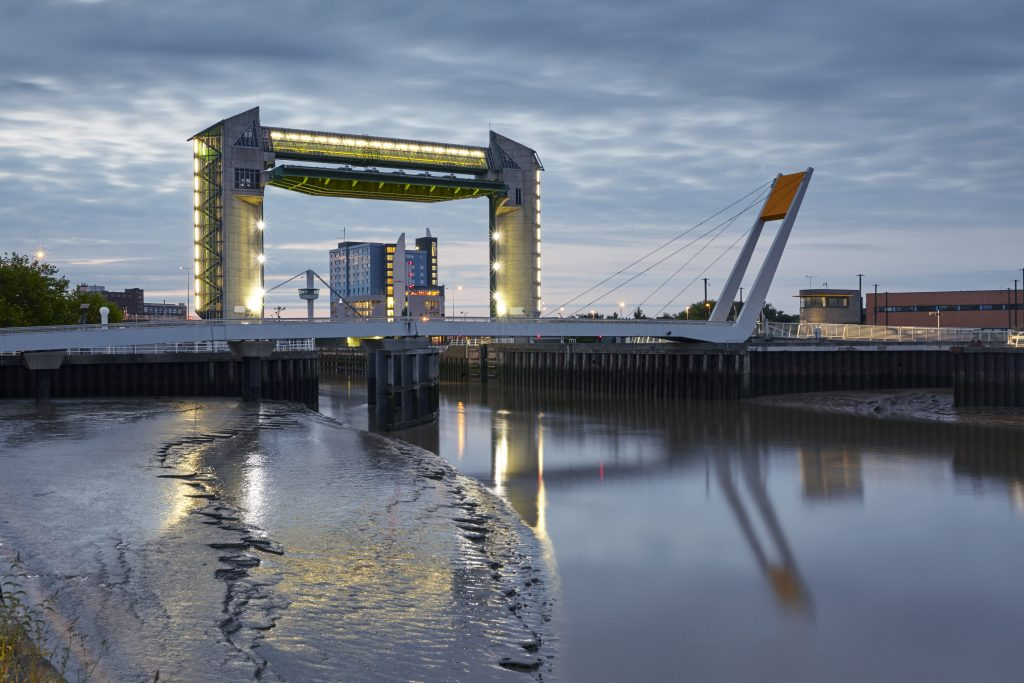 Hull's tidal defence barrier with the river Hull and pedestrian bridge in the foreground